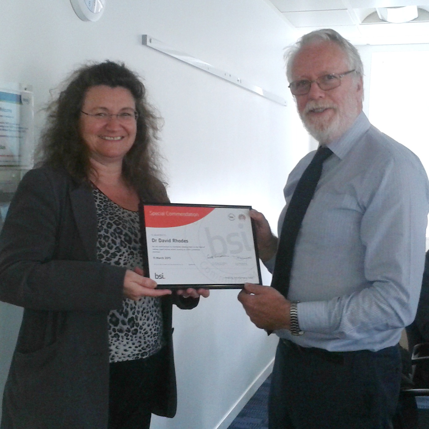 Dr David Rhodes (right) receives his award from Debbie Stead, BSI