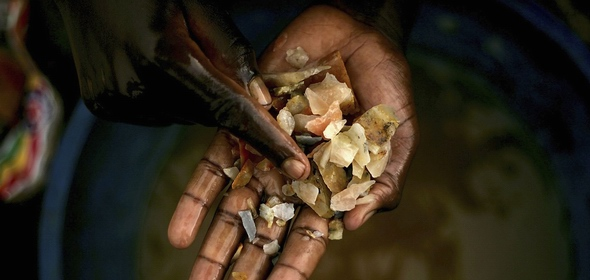 Boy in Congo sorts through rocks looking for gold.